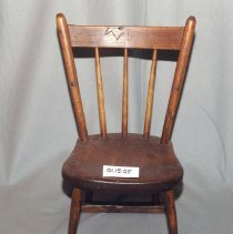 Image of 01.15.05 - child's chair.  Three vertical posts comprise the back.  The base has two boards running from front to back along the sides.  No front or back boards exist.  Bottom is unfinished.  Knife cutting are visible on the back top rest.