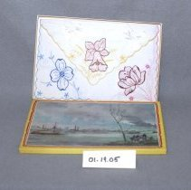 Image of 01.19.05 - A)  hankie box.  River landscape featuring cow, boats, mills etc. Three hankies are inside the obx. B)  hankie with blue embroidered flower on white material C)  hankie with  Yellow embroidered flower and sewn on material of pink and brown. D)  hankie