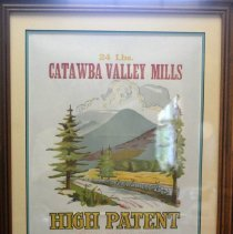 "Image of 01.25.04 - Framed Flour Bag from Catawba Vallye Mills. Reads ""24 Lbs  Catawba Valley Mills High Patent  Fincastle, VA  Bleached, Phosphate added""  Image features mountains, pine trees; and river and road lined by stones and wooden fence."