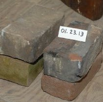"Image of 01.23.13 a,b,c,d - A)  Regular brick. 1/4"" line border around top.  Mortar attached. Light orange color. B)  Unidentified black material is attached to brick C)  One edge is glazed.  Mortar or plaster is attached. D)  Mortar or plaster is attached.  Yellow paint residue"