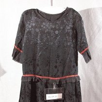 """Image of 06.04.01 - Manufactured black damask  dress with a round neckline bound with self fabric bias strip.  33 1/2"""" dropped waist with fluted trim joined with woven 3/8"""" rust and black trim.  3/4 sleeves measuring 13"""" also ending with fluted trim and also having the woven 3/8"""" rust and black  trim.  Skirt measures 25 1/2"""" and bodice measures 18 1/2"""" from shoulder seam to waist seam.  Left shoulder opening with plaket and 1 snap. Left side opening with  7 snaps.  Label found on left seam marked Size 16."""