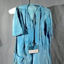 """Image of 06.04.02 - 42"""" long light blue silk dropped waist manufactured shift type dress with drop shoulder seam and short sleeves. The sleeves and dress hems have been shortened with an extremely poor sewing job. Front placket is closed with snaps and has two verticle tucks on either side of opening.  Torn belt loops on either side of the dropped waist with formed pleat on either side from waist to hem.   No belt with dress.  One exterior pocket on the right side of dress."""