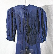 "Image of 06.04.03 - Navy dressing gown measuring 31 1/2"" from middle back neck to hem.  Waist had fabric trim which has mostly been cut away.  the 3/4"" sleeves measure 15"" from top of sleeve seam to bottom of cuff.  Beautiful sleeve seam detail; band type cuff with short sleeve placket  and two snaps closing at cuff.  Open down entire front with bodice trimmed with a 1/2"" ruffle down either side of placket.  Possibly had a closure at neckline did have a snap or hook and eye at waist. 3 small darts at center back."