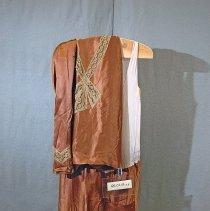 "Image of 06.04.04 a,b - Manufactured two piece copper colored ling sleeved silk crepe dress.  The 24 1/2"" top (from back neck to hem) is in an overshirt style with 1 1/2"" beige lace trim starting at shoulder seam coming to a ""V"" lace is cutout to show beige under fabric--the lace forms a 3 piece mock tie at mid-boddice.  The square-topped yoke is snapped at left side under lace trim with a plackert with 2 snaps.  Back has a yoke.  Two darts at bust line and a open dart at either side of shirt.  The 1 1/2"" beige lace is in a ric rac style, slightly above the hem of both sleeves.  The skirt is poorly  attached to a chamisole-type top of beige crepe measuring 37 1/2"" from neck to hem.  The skirt boosts a beautiful left side kick pleat."