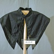 """Image of 06.04.08 - Black """"V""""  cape-style collar that was pinned to the black bodice #06.04.06.  This collar is 3 pieces sewn together to form the cape style collar."""