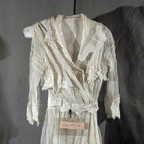 Image of 06.05.08 - White net dress (lined with same material) with appliques around collar, waist and hem.  Measures 53 inches from back collar seam to hem.  Snap front closure on bodice but skirt snaps at side.  Tuck darts front bodice and tucks at crown of sleeves.  Sleeve ends with decorative edge from appliques.  fabric and applique band front bust line stopping at front placket.