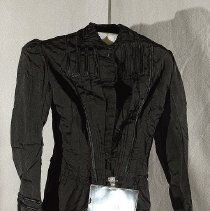 "Image of 06.05.11 - Black satin jacket with bustle back and hip emphases.  28"" long fron center back to hem.  Lined in brown.  Tucks and satin trim down front , collar, and long sleeves.   18 button closure with buttons grouped in 3's (only 8 braided satin covered buttons left.  4 bone stays down either side of front ."