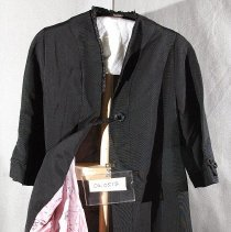 "Image of 06.05.12 - Black Jackie Kennedy type coat of  grosgain-type fabric with 1 decorative black button with braided thread loop closure .  3/4"" sleeves ending with piping type trim.  Stand-up shawl type collar with very decorative trim.  Pink lining with floral and eiffle tower print .  Coat 38"" long from  center back collar to hem"