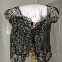 "Image of 06.05.16 - Black  lace bedjacket or undergarmet with short lace cap sleeves ending in brown scalloped sewed .  Top yoke in front and back very decorative open weave lace.  Waist band has drawstring.  Front opening with drawstring tie at neck and hook and eye closure down front placket.  Measures 15"" down center back."