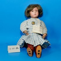 """Image of 03.01.86 - Schoenhut doll. A 16"""" inch tall girl doll with a brown hair and eyes. She is wearing a blue and white gingham dress with red shoes and stockings. Mary named the doll Drucilla.  Toy"""