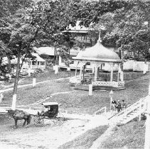Image of Photo0038.jpg - Bandstand, buildings, and lawn at Rawley Springs Hotel.  Three unidentified white males shown on the right beside steps;  unidentified black male shown in buggy in center.