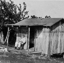 Image of Photo0088.jpg - Man in front of shack behind Ed Friddle's filling station