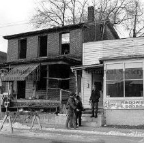 Image of Photo0105.jpg - Two small buildings with three men on the front stoop. Harrisonburg Police station is to the left.   These buildings are located on the southwest corner of the intersection of West Water Street and Liberty Street in Harrisonburg, Virginia