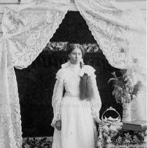 Image of Photo0153.jpg - Young woman with long hair hanging down the front of her white dress, standing next to a table