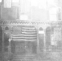 Image of Photo0160.jpg - Strayer house with various flags adorning the front, located on East Market St. and later replaced by the Dale Wenger Chevrolet show room.