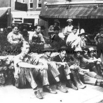 Image of Photo0170.jpg - Men sitting on sidewalk and embankment in front of Keezell building in Harrisonburg