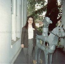 Image of Photo0180.jpg - Amy Johnson, director of the Warren-Sipe Museum on a front porch with sheet metal horse.