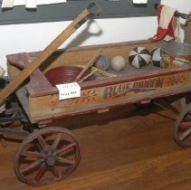 """Image of 03.01.849 - Child's red metal wagon with """"Blue Ribbon"""" stenciled on each side.  Wooden pull handle with metal grip and four metal wheels.  Fair condition, paint is faded."""