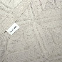 Image of 03.01.866 - Cream-colored bedspread.  Machine made knit squares with seven squares across and eight squares deep with trim all around.  Fair condition, stain on left side near top.