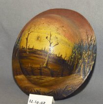 """Image of 12.10.02 - A metal painted helmet used in World War I by Walter G. Simpson, 80th Division 313 Field Artillery Battery A. It was painted at the IH (International Harvester) dealer in Clarksburg, West Virginia during the Depression by a local artist. The scene painted on the outside of the helmet is of a field with a barbed wire fence, leafless trees and a brown earth (ground). The chin strap and the fitted head gear is in tact inside the helmet. Inside the brim of the helmet say """"WALTER G. SIMPSON 1.833.484 80TH DIVISION, 313 FIELD ARTILLERY BATTERY A    SOMEWHERE IN FRANCE.   The daughter of Mr. Walter Simpson believes that the painting was copied from a photo in an album that showed a photo when his unit was in France."""