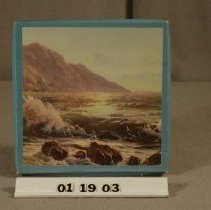 Image of 01.19.03 - Hankie box with blue border.  Ocean landscape with mountains in the background adorns the front.  Box is empty