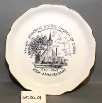 """Image of 05.06.01 - A porcelin commorative plate with a picture of a church with shrubs and trees. Underneath the picture, it says: 1763-1963, 200th Anniversary.  Around the top of the picture it says: Brown Memorial United Church of Christ, McGaheysville, Virginia. On the back of the plate it says: The Sabina Line  Warranted 22K  Made in U.S.A. The plate measures 10"""" in diamater and has scalloped edges rimmed in gold. The back also has a name tage of George Hedrick."""