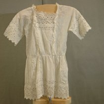 Image of 06.03.01 - White cotton little girl's  short sleeved dress with self eyelet trim on hem, both sleeves and yoke.  Lace trim between yoke and bodice of dress both front and back.  Snap closure down right side of yoke.