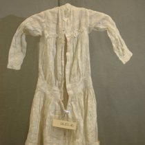 """Image of 06.03.02 - White little girl's long sleeved dress with banded drop waist, gathered to form trim between yoke and bodice of dress  and 3/4"""" band at neck.  Material has small open weave squares. Material is gathered at hem. Opening down back with 3 button holes directly under band at neck, 1 button hole at junction of yoke and bodice and two at waist band.  No buttons remaining on dress."""