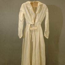 """Image of 06.03.03 - Plain long wool dress; front opening;  banded waist  with cartridge pleating all the way around the waist of the skirt.  Plain buttons (6 spaces only 1 remaining) on placket  but no button holes on placket  (missing placket?). Center pleats on the bodice waist at center front and center back.   Deep 9"""" faced hem.  Hook and eye on waistband.  Had laundry tag stapled in dress with WINE printed on it which we removed.  A real mix of hand and machine sewing."""