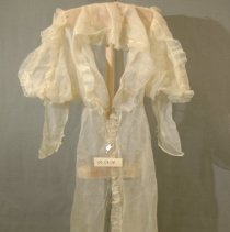 """Image of 06.03.04 - Sheer crinoline dressing gown, very dressy--most likely wedding trousseau.  Open in front with only hook and eye at waist closure, shawl collar to waist with 1 1/2 ruffle.  Rufflle continues down front to end at hem.  Long mutton type sleeves with puff  made of 4 panels front two with 1 1/2"""" ruffle like front.  Pointed hem with 5 loop and button closing at  both wrists--only a total of 5 fabric covered buttons left from both sides.  Center back with 3 small darts and gathered waist in front straight in back."""