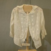 """Image of 06.04.05 - Bodice  white lawn material.  Has front opening with thread covered buttons (6 but 2 are missing)  Hem of boddice is a 3 1/2"""" band.  3/4"""" self sleeves end with 1 3/4"""" gathered cuff.  Material of bodice has manufactured embroidered design 1"""" long.  Right placket has open weave down one side. Dropped shoulder detail is also in an open weave design.  Collar ends in a """"V"""" Point at each shoulder another """"v"""" point at front of collar."""