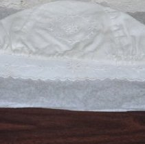 Image of 01.20.03 - White baby's bonnet.  Eyelets embroiedered aroudn face, ridged along border.  Back of bonnet has embroidered circle enclosing a pattern.