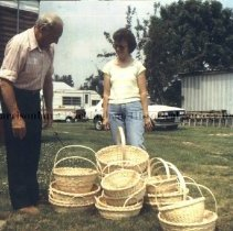 Image of Photo3049.07.jpg - John and Dorothy Nichols standing with stack of finished baskets