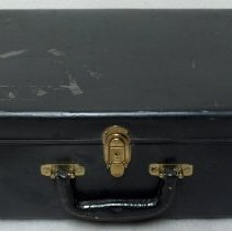 Image of Suitcase; black paper fiber suitcase with brass colored hinges; 1960.