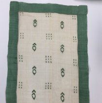 Image of Rectangular doily with green border and abstract designs in center; 1920.