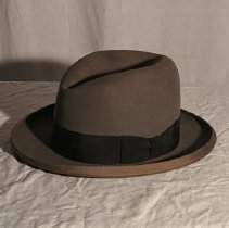 "Image of Homburg hat of dark grey wool felt; black grosgrain ribbon band, with bow on proper left side. Grey grosgrain binding on brim edge. Interior band of leather, stamped in gold, ""Savard Bros. / SARATOGA SPRINGS, N.Y."" Crown lined in white silk satin, printed under a crest, ""Royal De Luxe / STETSON"". - Homberg"