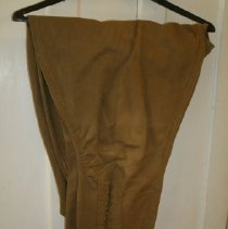 """Image of a--Tan, cotton twill """"riding breech"""" style trousers, four button fly, hook waist, lace-up cuffs.  Pants have two front pockets and a """"watch"""" pocket with """"USA""""  raised letters on buttons.  (see 81.17.90b)    - pants"""