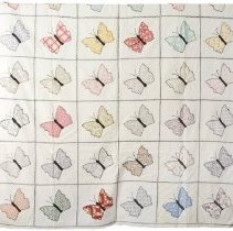 """Image of Appliqued summer quilt of white muslin and scraps, background divided by black feather stitching into 42 squares each having an appliqued butterfly.  Butterly bodies are black embroidered cotton with embroidered antennae.  No batting  Butterfly quilt donated by Brookside Quilters, purchased at auction in Saratoga, NY from owner Ralph Craw.       Quiting Group recorded 10-23-10: Finished coverlett/summer quilt, butterflies, Brackman #51.18(7?) variation, straight edged in muslin colored, multi-colored pastel color scheme with some embroidery thread broken and a small spot, block pattern with butterfly subject, with 42 quilt blocks, each 10.5"""" by 10.75"""" in a straight orientation and square block style, no border, cotton fiber type with broadcloth, muslin, and possible bias tape in butterfly body fabric types used, solid/plain fabric pattern, hand pieced, with decorative applique stitch, hand appliqued. Back made of cotton in cream color, in two pieces (30.5"""" and 35.25""""). Binding turned back to front, no batting, not quilted, with black embroidery thread. Appliqued and embroidered summer quilt/coverlet with no batting.                                                                                                                  - quilt"""