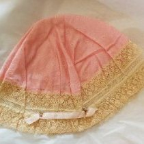 Image of Boudoir cap with pink crown, woven with diamond pattern. Off-white lace edging, to which is sewn a segment of pink ribbon - Cap, Boudoir
