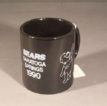 Image of Cylindrical body with large ear-shaped handle.  Black slip with white lettering and line drawings.                                                                                                                                           - mug
