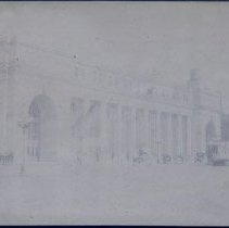 Image of Great Northern train station with horse & buggy.  Very early cars, street lined with gas lamps.  People walking on sidewalk.  An electric cable car is just before a second building, The Great Northern Freight Station.  Notice on top of the building the water tower and advertisements.  Time on clock 1:20. - 1997.016.0044