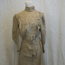 Image of Day dress of tan linen. High collar; buttoned opening down proper left front angling tward center. Buttonhole edge is scalloped and  trimmed with braid. Bodice tucked over shoulders. Full sleeves, pleating into self-fabric and braided cuff with decorative button. Two rows of buttons up from the front hem of the skirt. Slight train. - Dress