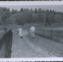 """Image of Photograph (black and white) of man and woman walking towards a road. The back of photo has a series mark  of """"122"""".  - 2011.036.0115"""