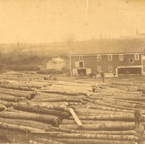 Image of Logs by Seabury sawmill, Galway.  Boy standing on log in foreground.                                                                                                                                                                                           - 1968.018.0034