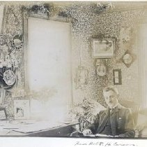 Image of Informal portrait of the Rev Robert H. Carson at his desk, prob. Stillwater.  Christmas decorations.                                                                                                                                                          Folder also contains 1978.122.0016B - 1978.122.0016A