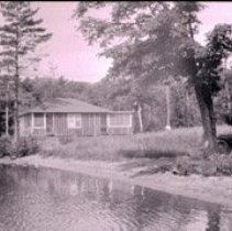 Image of Negative of a snapshot of a house by a shore.  Possibly Lake George. Streever Collection.                                                      - 1979.114.1040