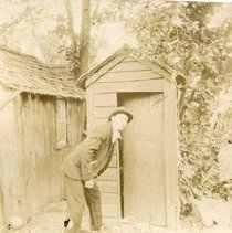 Image of Identity of man unknown.  Valuable because it shows an outhouse (latrine) and part of a shed.