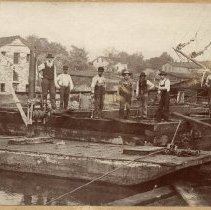 "Image of Building the crib for the east pier, May 29, 1903 - Men working on the ""L"" shape portion of the east pier."