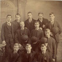 Image of Eleven Unidentified Young Men dressed in dark suits. - Potential names include: F. H. Armstrong; W. Wales; William Wass(?); Mervin or Chas Armstrong(?); John Whitaker