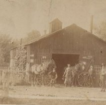 Image of MacDonald's Blacksmith Shop - Sandy MacDonald's Blacksmith Shop, with George MacDonald; Sandy MacDonald, George Wilson etc. posed in front  Located on Thomas Street North, east side, north of alley.  Alternate location may be north side of Colburne, west of Trafalgar, behind the buildings facing Colborne (Lakeshore Road)  Later Al. Kemps